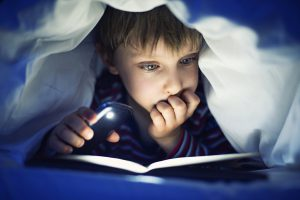 Little boy aged 5 is secretly reading book under sheets using mobile light. The book is very interesting and the boy is quite lost in it.